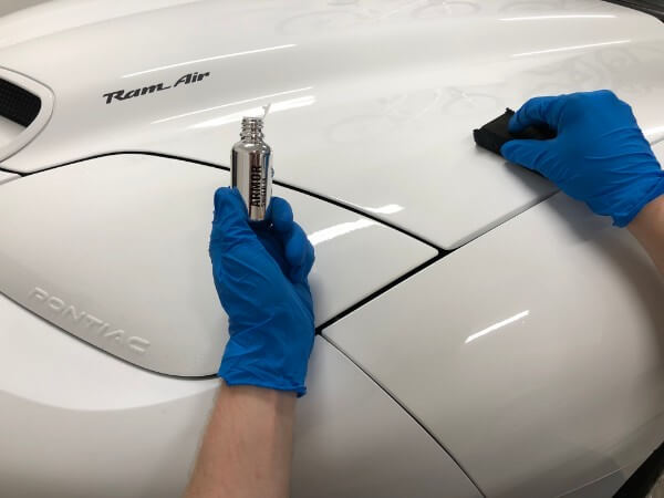 wiping AvalonKing Armor Shield IX ceramic paint coating on white trans am hood