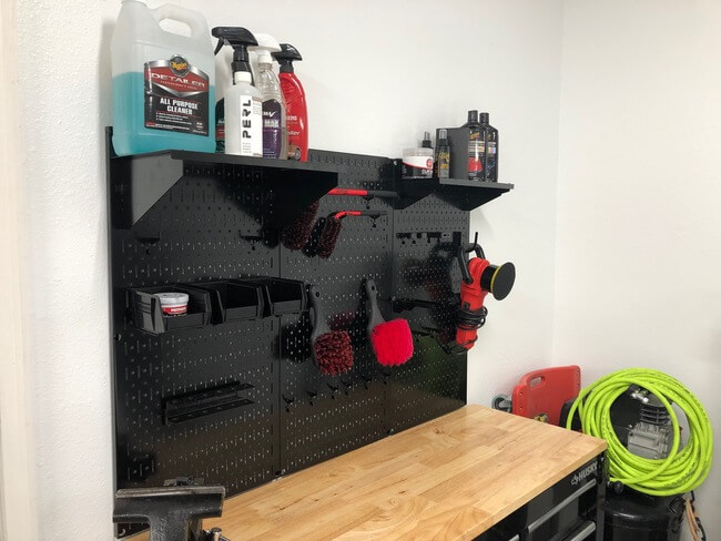 black wall control metal pegboard panels installed behind black husky workbench with black accessories