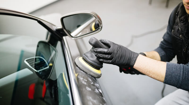 Man holding black dual action polisher with black polishing pad against grey car door.