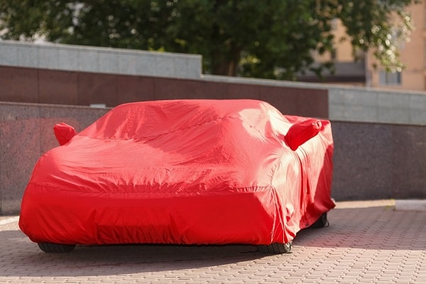 Custom-fit red car cover protecting from the sun outdoors.