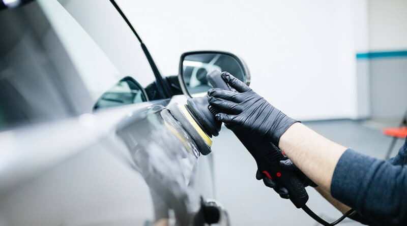 Man polishing side of grey car door with black dual action polisher with a black polishing pad on it.