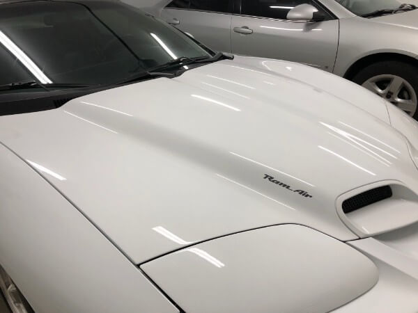 paint corrected white trans am hood with ramair sticker