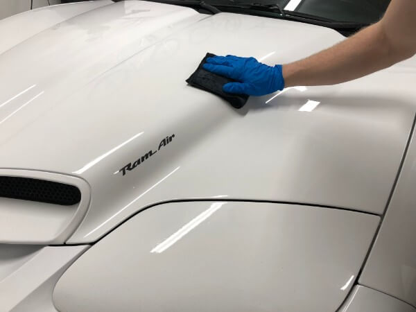 wiping away excess AvalonKing ceramic coating with included black towel