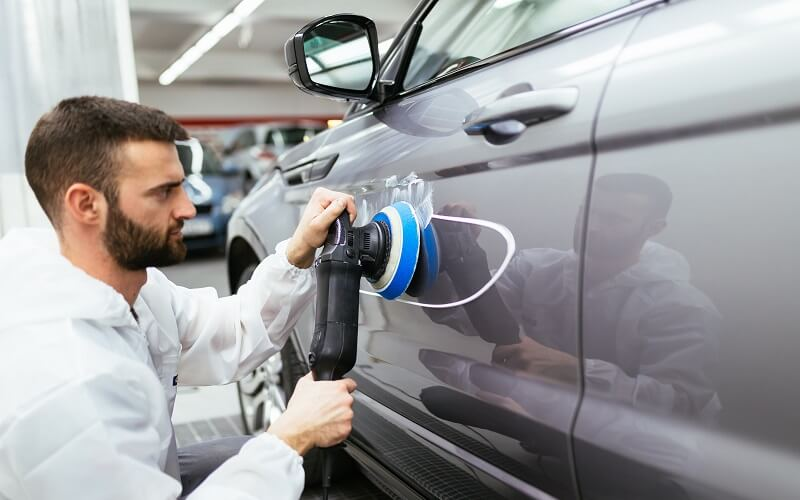 Man polishing side of silver car with black rupes polisher with a blue pad.