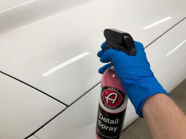 spraying Adam's Polishes detail spray onto white trans am hood