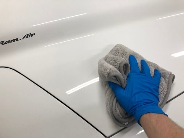 wiping hood of white trans am with Towel Titan Microfiber Wax and Polish towel